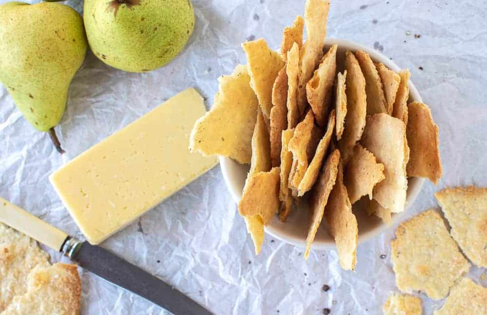 homemade crackers in white bowl with cheese and green pears