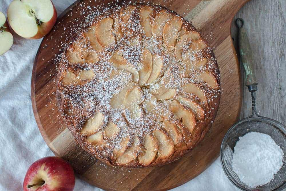 Apple cake on round wooden board with apples and icing sugar