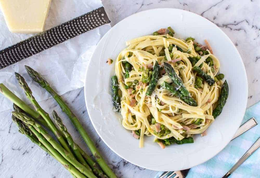 pasta with asparagus on white plate, fresh asparagus, block of cheese and grater
