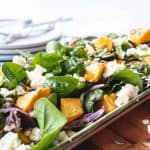 pumpkin and spinach salad on oblong plate on wooden board with plates and forks