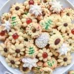 decorated spritz cookies on white plate with two little dishes of cake sprinkles