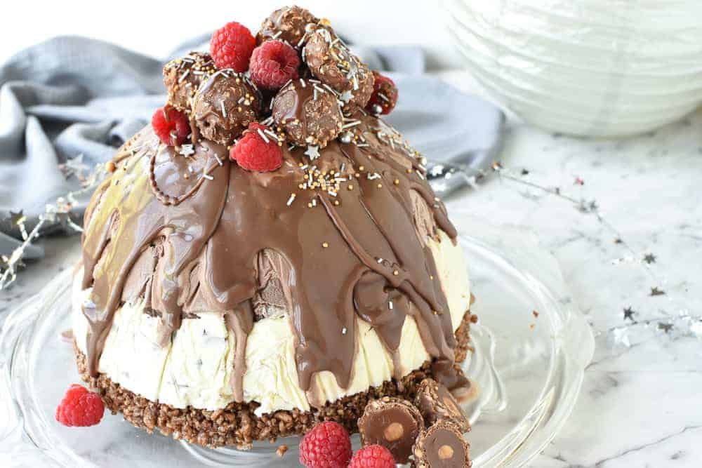christmas ice cream pudding with chocolate drip decorated with chocolates and raspberries