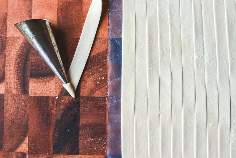 sheet of raw puff pastry cut into strips. one strip being winded around a cream horn mould viewed from above