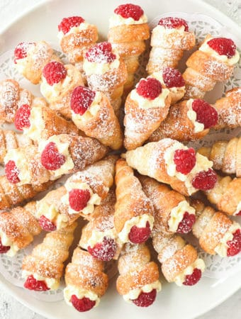 mini cream horns filled with cream and topped with raspberry arranged in a circular pattern on a round white plate viewed from above
