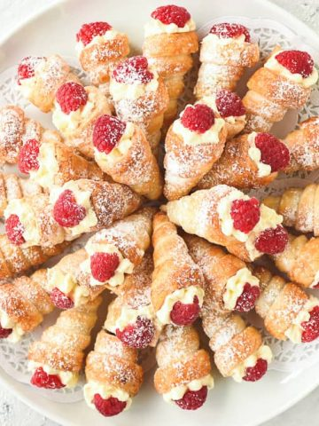cream horns filled with cream and topped with raspberry arranged in a circular pattern on a round white plate viewed from above