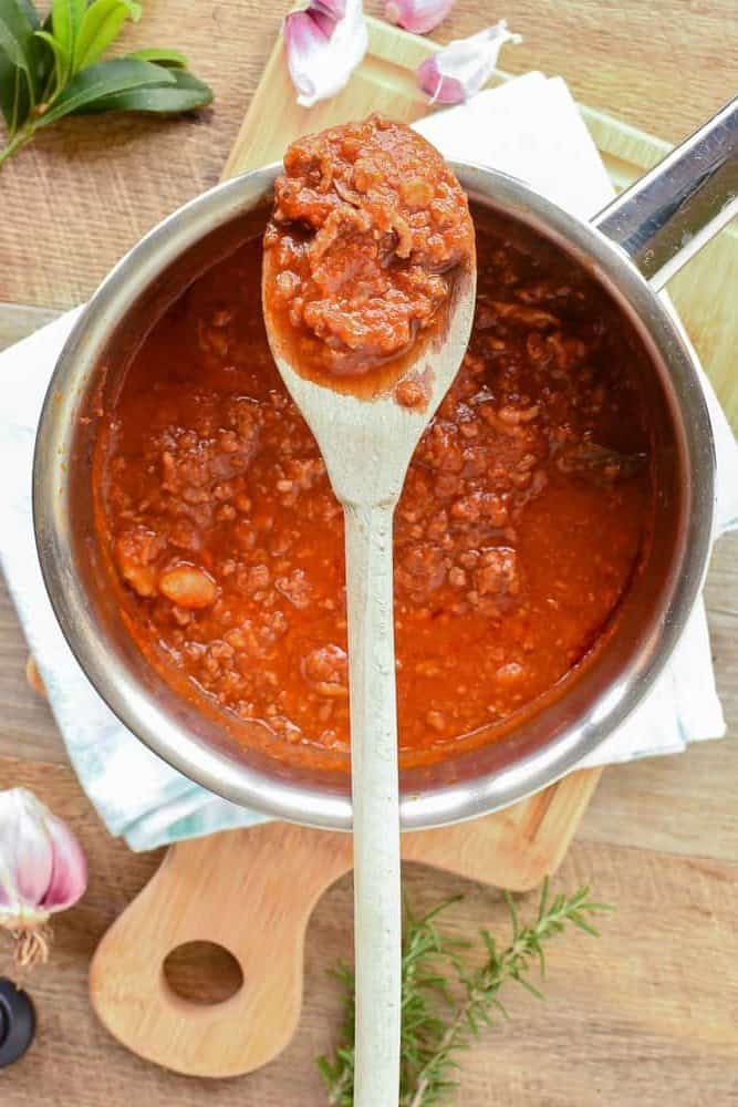 Saucepan of ragu pasta sauce with wooden spoon resting across the saucepan with some ragu pasta sauce on the spoon