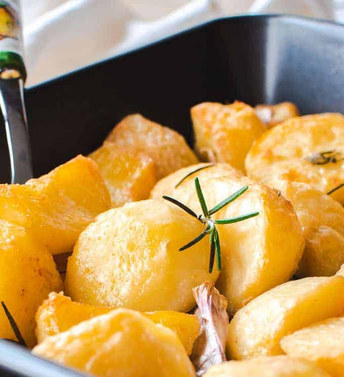 roasted potatoes in black oven tray with serving spoon