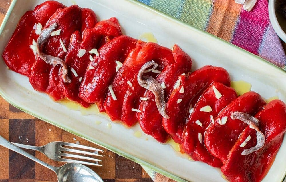 Roasted Red Peppers on cream colored platter with a drizzle of oil, anchovies and a chopped garlic viewed from above.