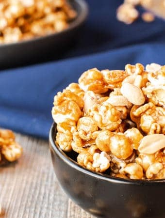 Homemade caramel popcorn in a grey bowl on blue cloth. smaller black bowl of caramel corn in background caramel corn and nuts on wooden table. close