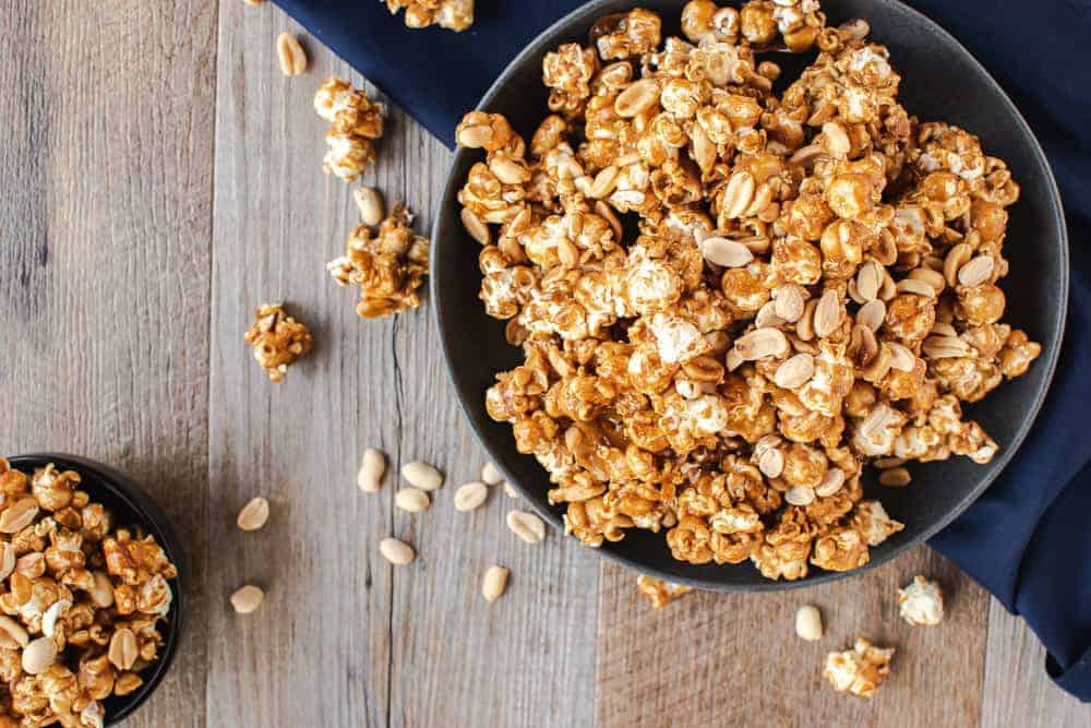 Homemade caramel popcorn in a grey bowl on blue cloth. smaller black bowl of caramel corn in background caramel corn and nuts on wooden table viewed from above