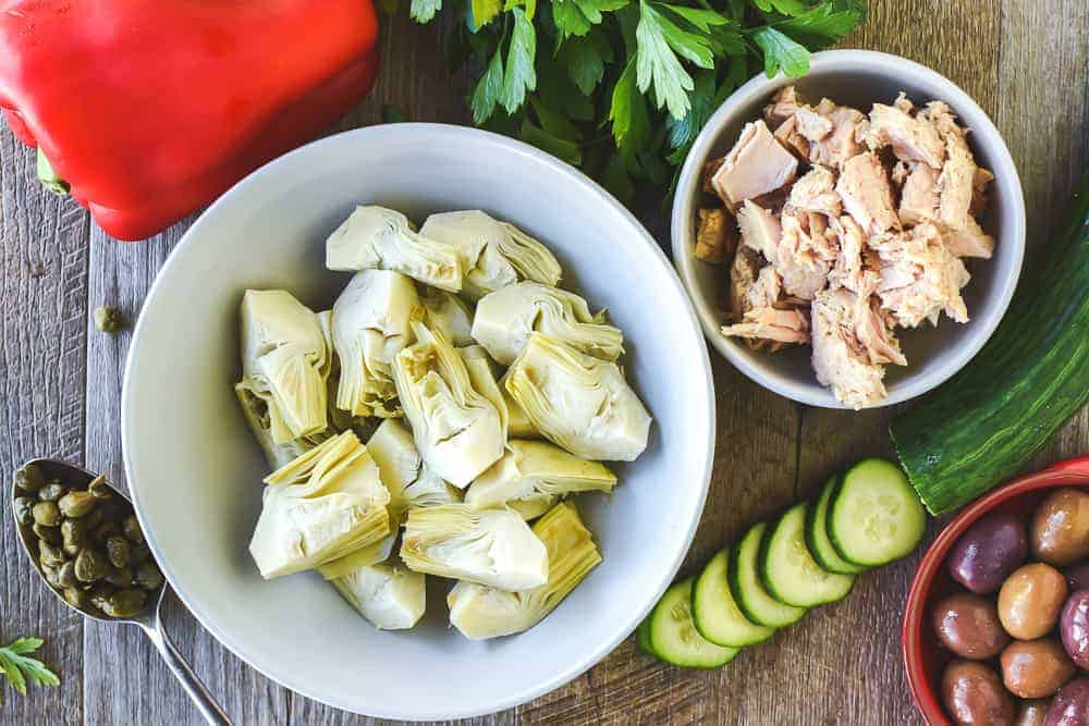 Canned artichokes in white bowl, red capsicum, parsley, canned tuna in white bowl, cucumber slices, black olive in red dish, spoonful of capers viewed from above