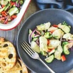 Artichoke salad on dark plate with fork, two slices of toasted bread, white pan with red trim filled with artichoke salad on wooden table with a grey cloth, viewed from above.