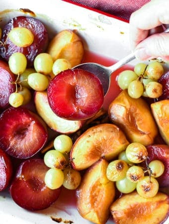 roasted plums, peaches and green grapes in white pan with red trim also hand spooning out plums viewed from above