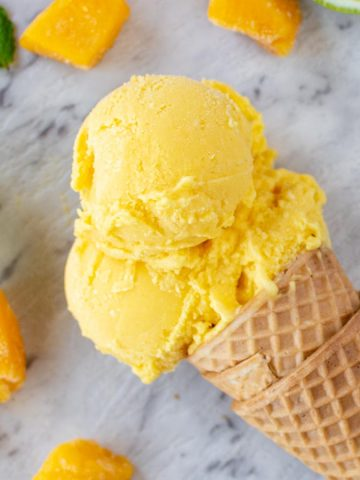 close up of ice cream cone with 3 scoops of mango ice cream on marble table, chunks of mango, lime cheek and mint leaves.
