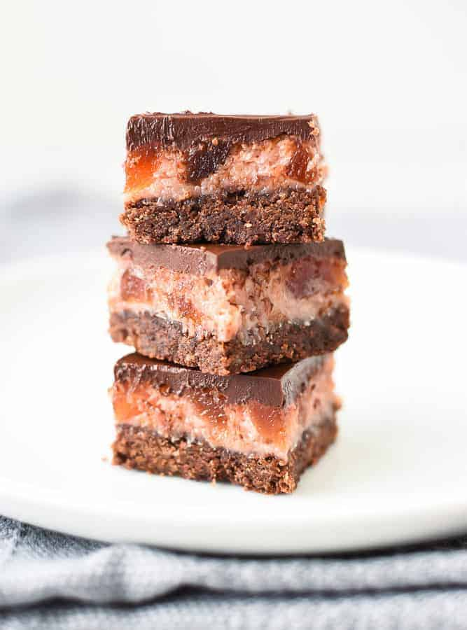 Three chocolate cherry slices stacked one on top of the other on a white plate viewed front on