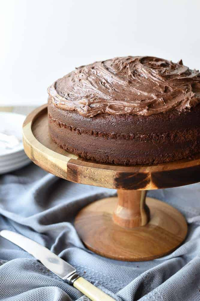 Frosted Chocolate cake on wooden cake stand