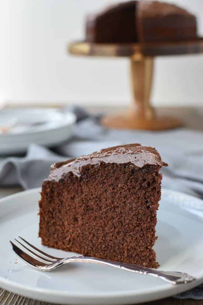 Slice of chocolate cake on white plate with cake fork, whole cake in the background.