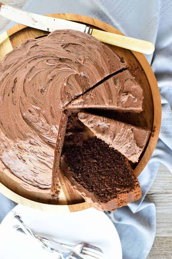 Chocolate cake with frosting and three slices cut viewed from above.