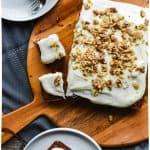 Carrot cake with cream cheese frosting and chopped walnuts on round wooden board with two squares of cake beside. Two white plates on either side with square of cake on.