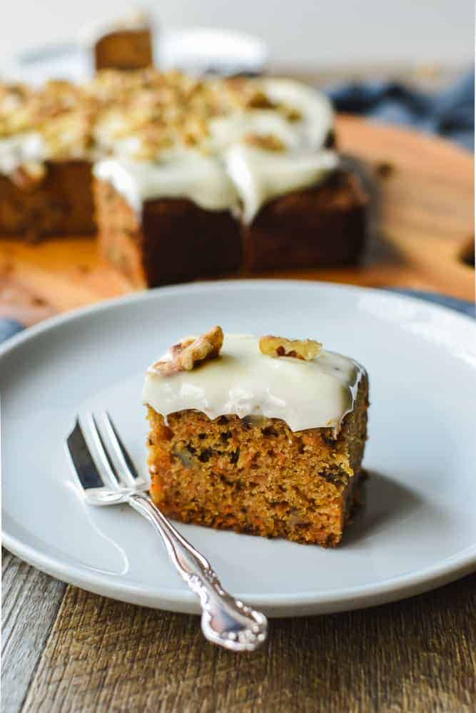 Square of carrot cake with cream cheese frosting on white plate with silver cake fork, remaining cake in background