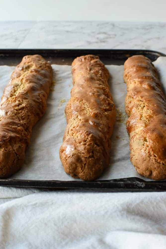 Three baked logs of biscotti on baking tray