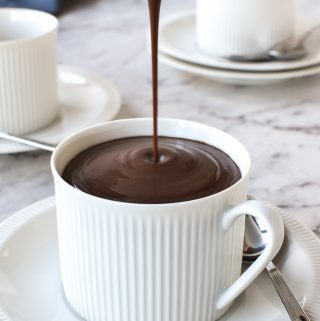 white cup and saucer being filled with hot chocolate poured from a white jug