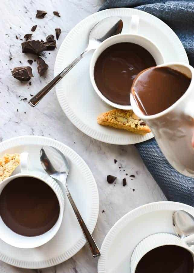 Three cups and saucers of hot chocolate and hot chocolate being poured out of a white jug