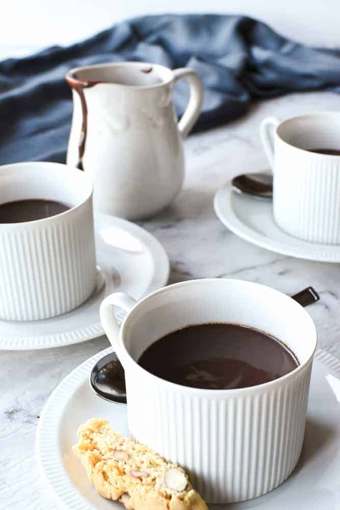 three white cups and saucers of hot chocolate with small white jug