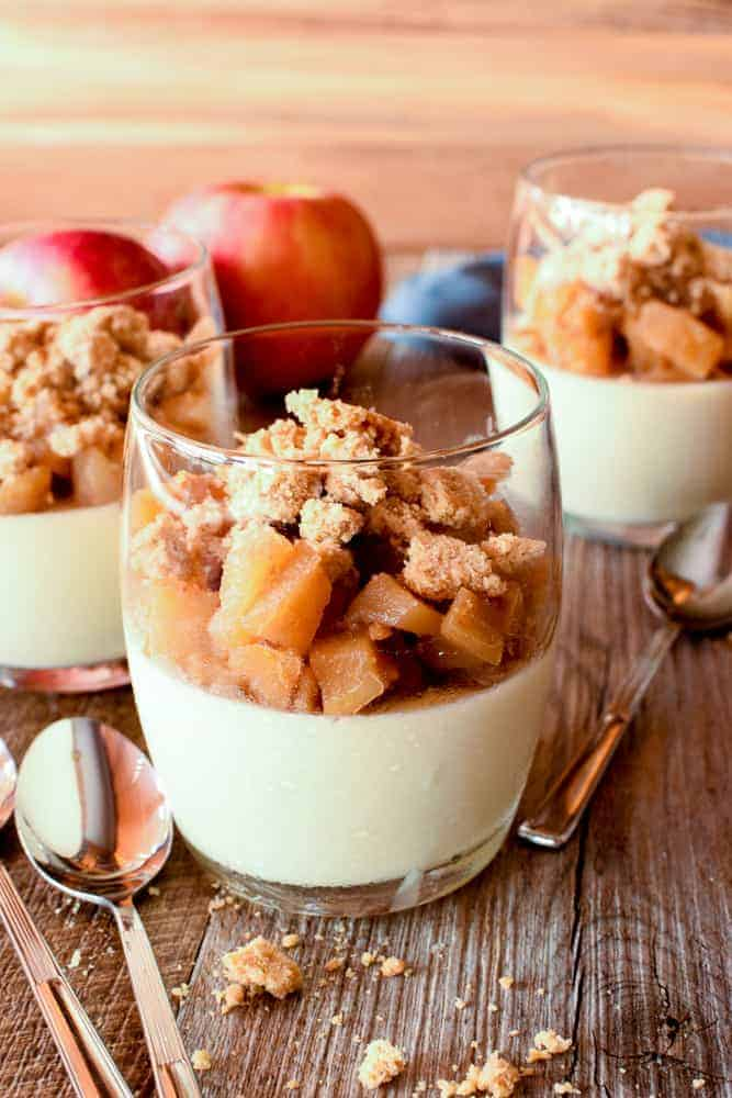 Three glasses of panna cotta topped with caramelised apples and crumble; two red apples in the background