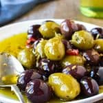 white plate of assorted olives viewed from the front