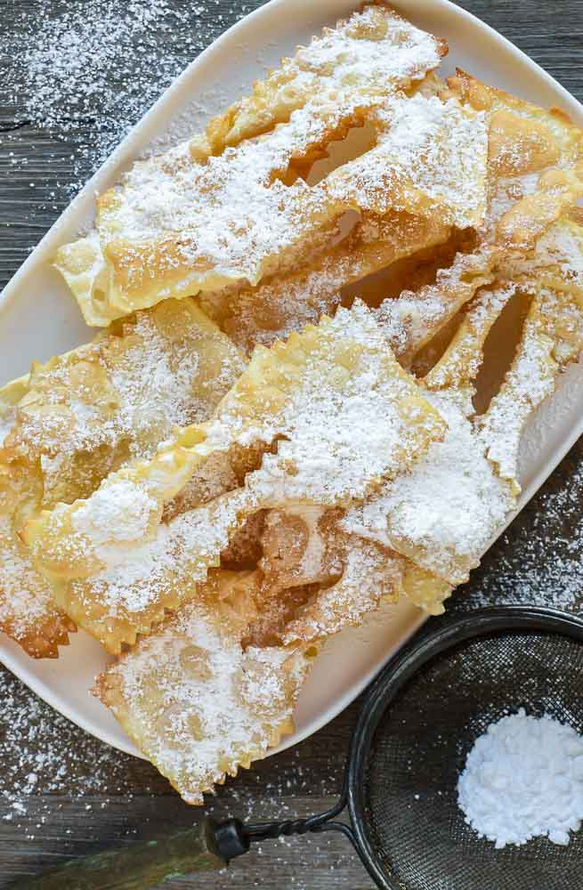 Fried Italian pastries - crostoli dusted with powdered sugar viewed from above