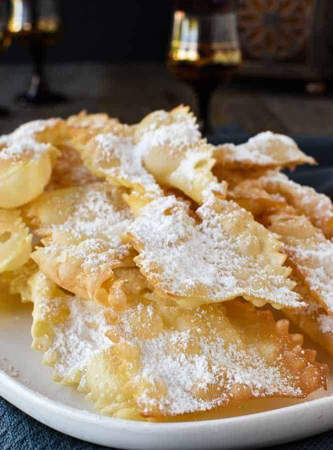 Fried Italian pastries - crostoli dusted with powdered sugar viewed from the front