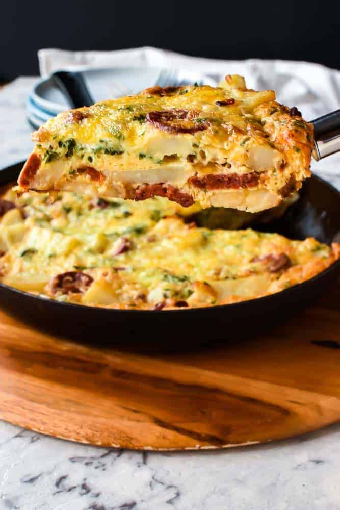 Slice of potato frittata being lifted from pan