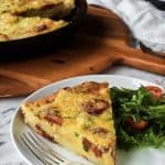 slice of potato frittata on white place with lettuce and tomato. black frypan of frittata in the background