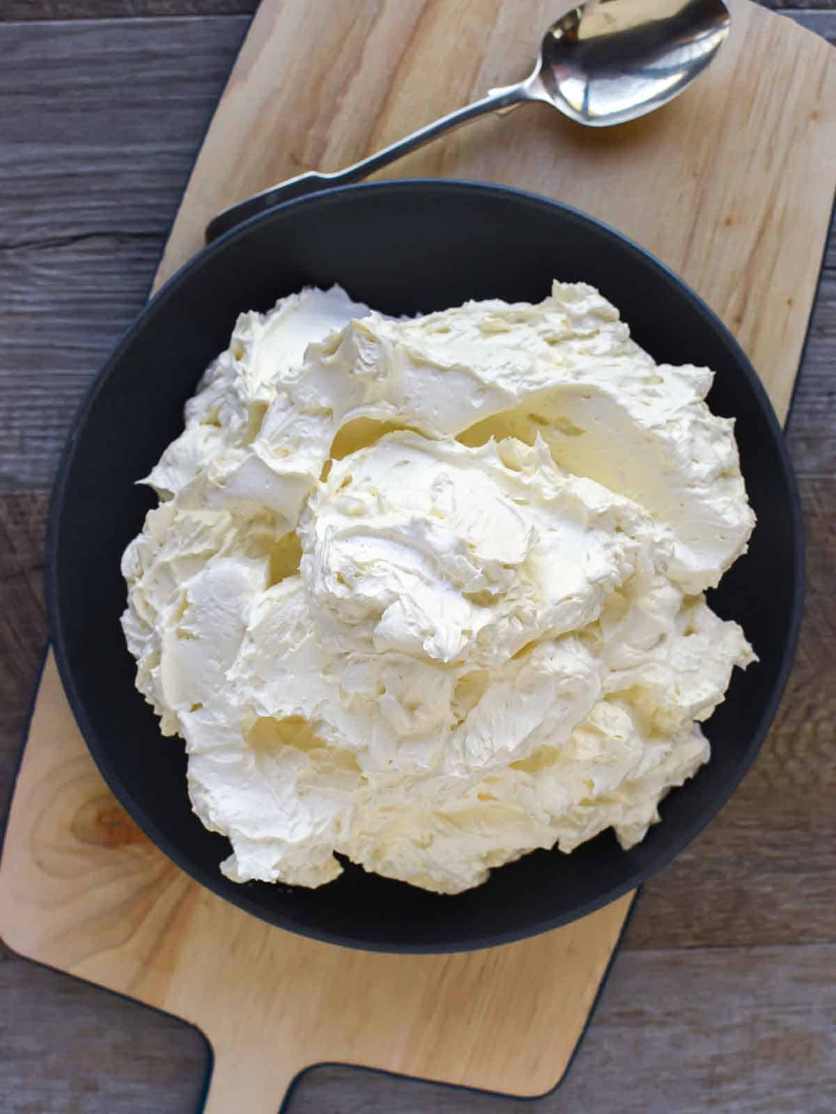 Italian meringue buttercream in black bowl viewed from above