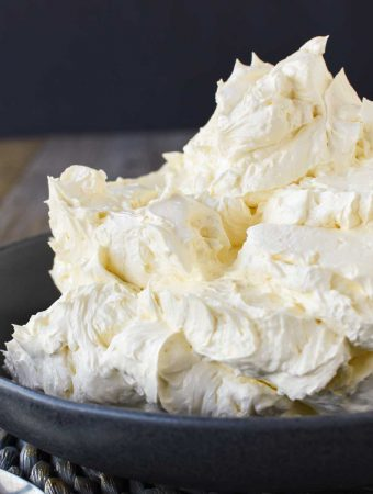 Italian meringue buttercream in black bowl viewed from the side