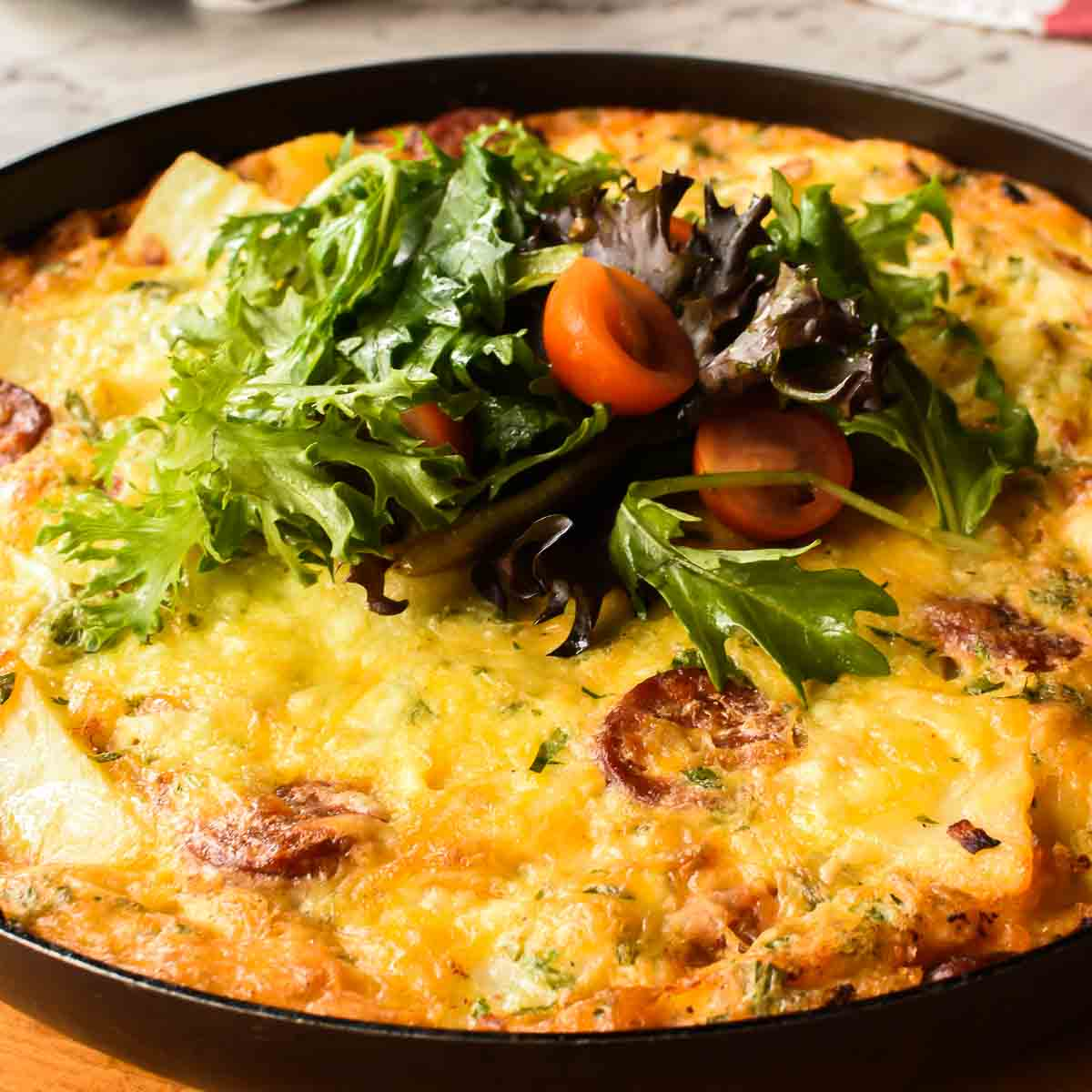 frittata in a black pan with lettuce and tomatoe pieces in the centre viewed from 45 degree angle