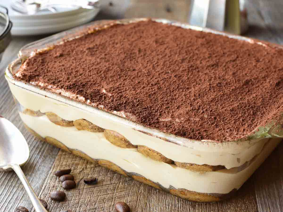 Tiramisu in square glass pan viewed from the side