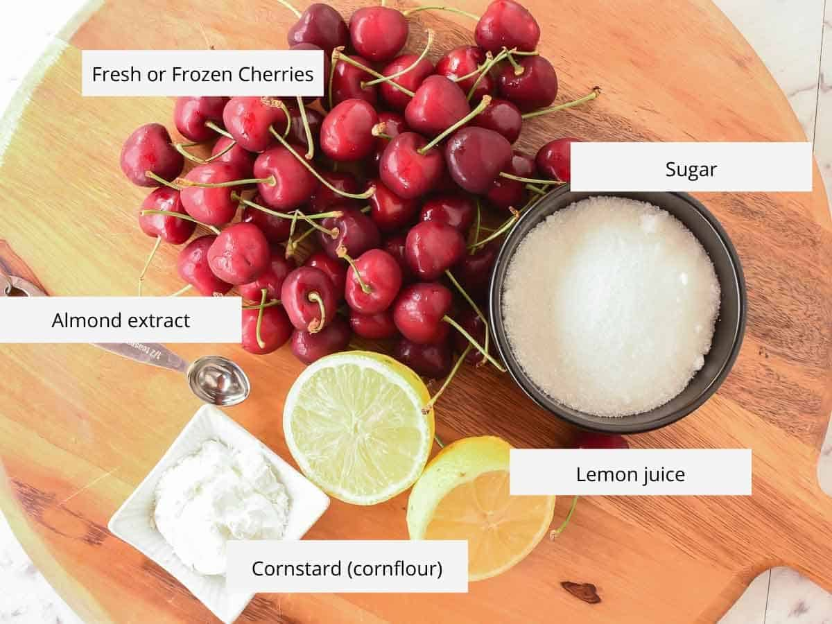 fresh cherries, sugar, cut lemon, metal spoon and cornstarch on wooden board viewed from above.