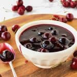 Cherry sauce in white bowl with cherries scattered around, spoonful of sauce beside bowl