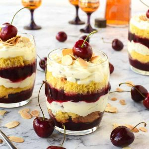 layered creamy cherry dessert in a glass with a cherry on top cherries scattered around and two other glasses of dessert in the background