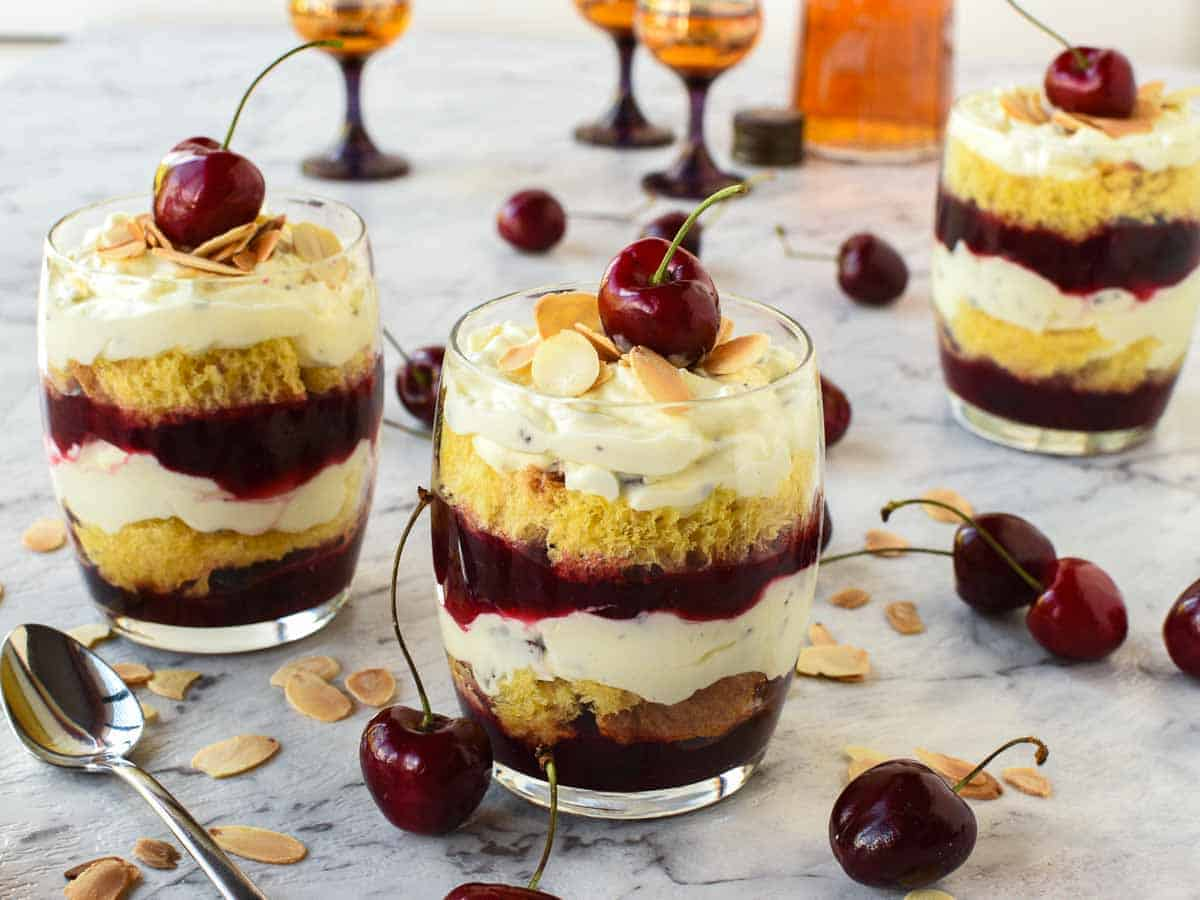 This is a Trifle dessert - layered creamy cherry dessert in a glass with a cherry on top cherries scattered around and two other glasses of dessert in the background