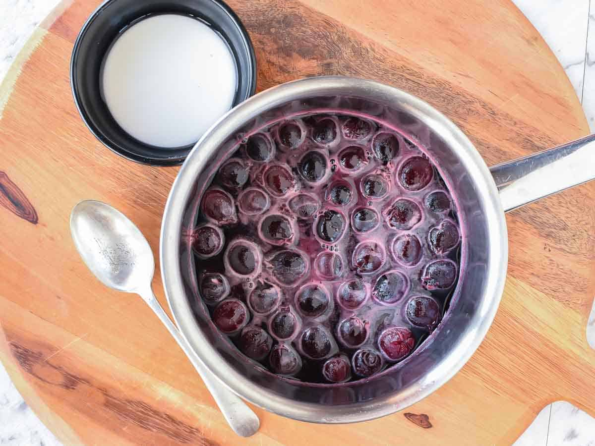 Cherries and liquid in saucepan with white cornstarch slurry in black bowl and metal spoon beside viewed from above.