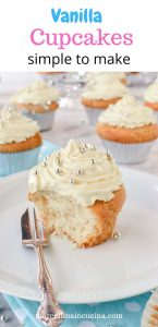 Half a cupcake with white buttercream on a white plate with silver cake fork.