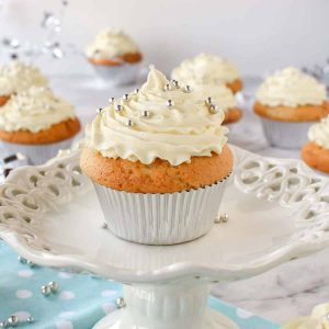 Cupcake with white buttercream on small white cake stand on blue polka dot cloth and cupcakes in the background