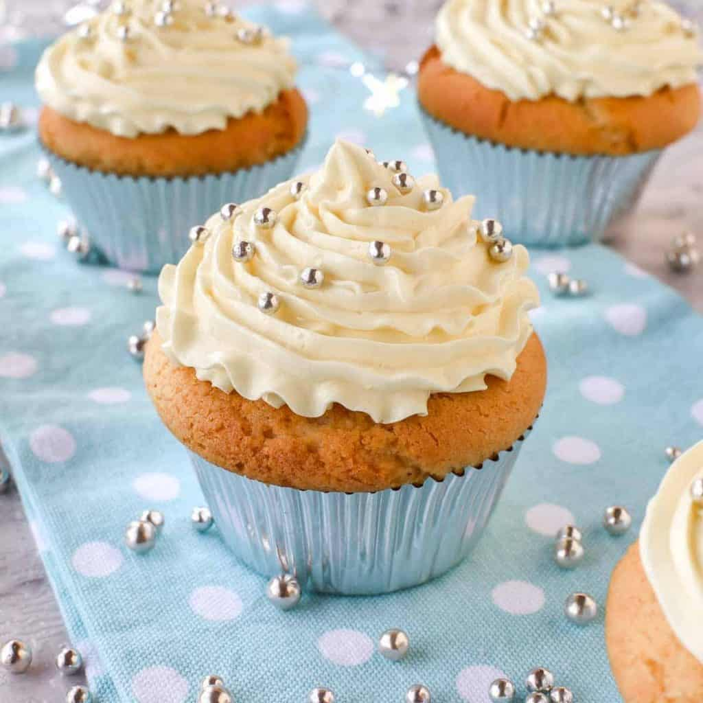 cupcake with white buttercream on blue polka dot cloth with cupcakes in the background with silver balls scattered around