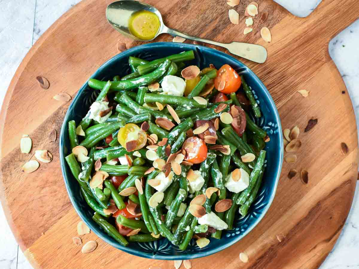 green bean salad with tomatoes and feta in blue bowl on wooden board viewed from above