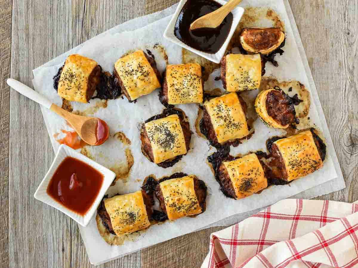 sausage rolls on baking paper with black sauce and red sauce viewed from above