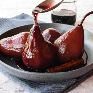 4 red wine poached pears in grey shallow bowl with spoon pouring red syrup over a pear