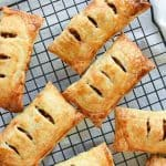 Image with text - image is 8 puff pastry apple turnovers on a black wire rack viewed from above